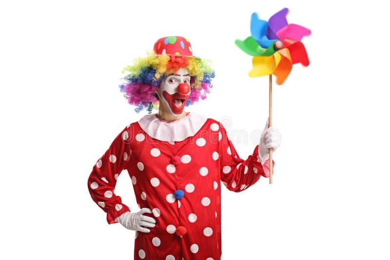 拿着五颜六色的轮转焰火和看照相机的快乐的小丑 免版税图库摄影