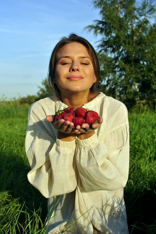 拿着亚麻布衬衣草莓的女孩 免版税库存图片