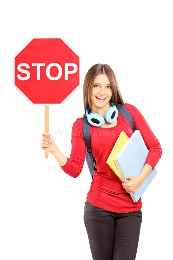拿着交通标志的微笑的妇女停止和笔记本 库存图片