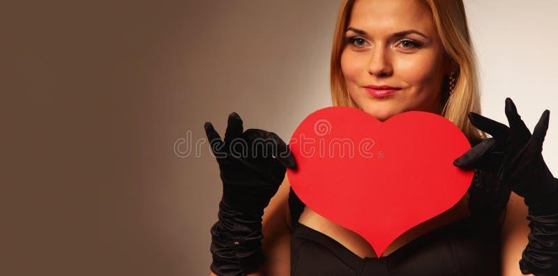 拿着人造心脏的美丽的妇女 库存照片