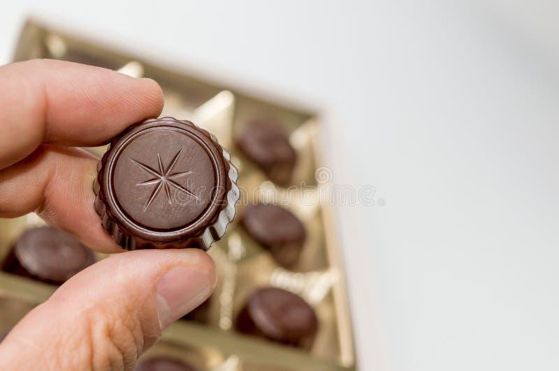 拿着从一箱的一个人的手巧克力巧克力 库存照片