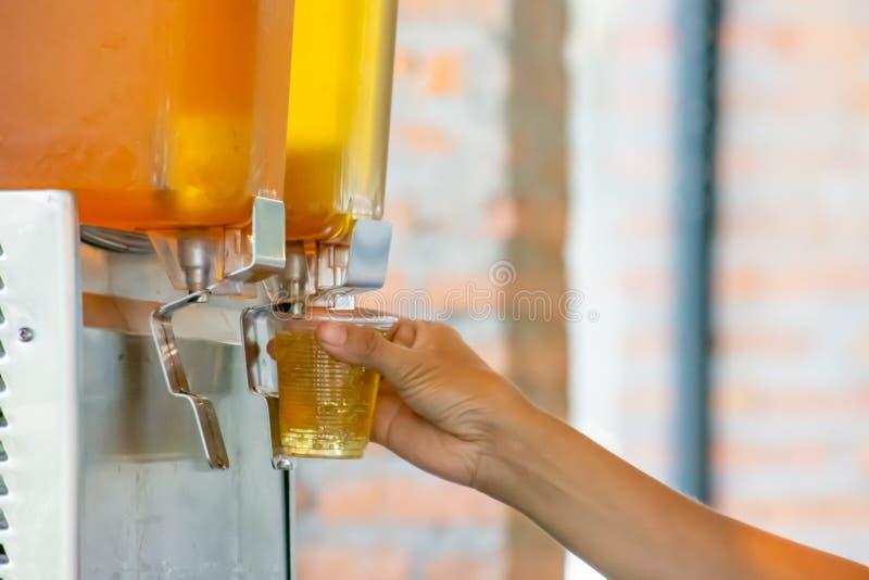 拿着从汁液Dispensor的手杯子塑料充足的茶 库存照片