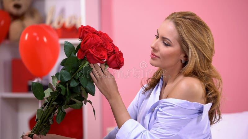 拿着从秘密钦佩者的沉思妇女玫瑰在情人节,惊奇 免版税库存图片