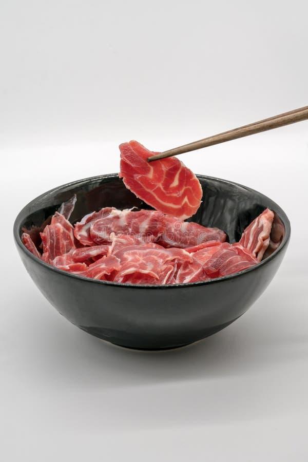 拿着从黑cerami的筷子新鲜的被切的牛肉后面小腿 免版税库存图片