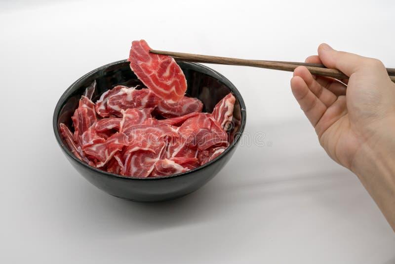 拿着从黑cerami的筷子新鲜的被切的牛肉后面小腿 免版税库存照片