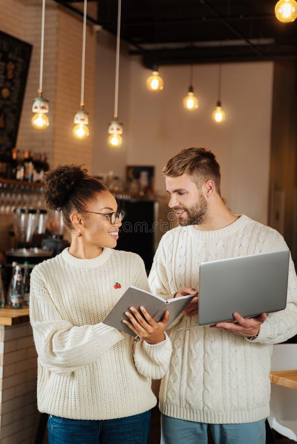 拿着他们的膝上型计算机的年轻商人站立在他们的咖啡馆 库存图片
