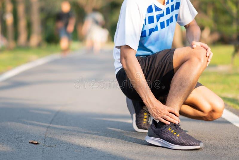 拿着他的体育腿部受伤的年轻健身人 肌肉痛苦在训练期间 有亚洲的赛跑者脚腕疼痛和问题以后 免版税图库摄影