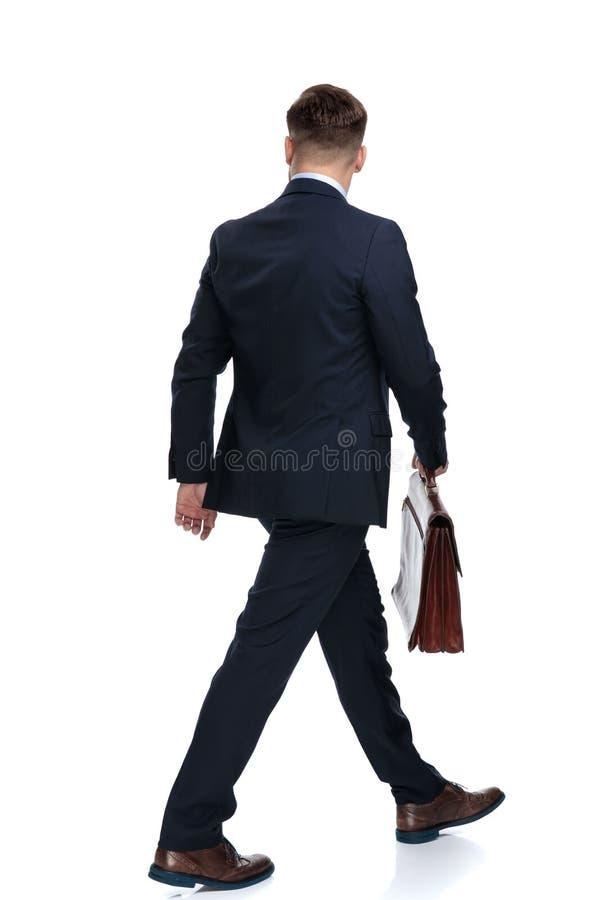 拿着他的公文包的一个走的商人的背面图 库存图片