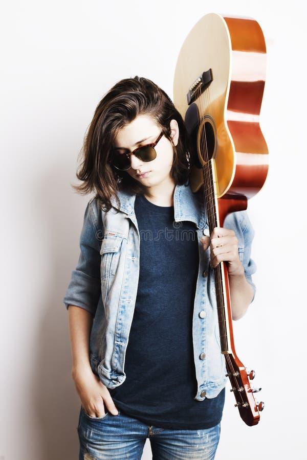 拿着他的在肩膀的英俊的少年画象吉他 免版税库存图片