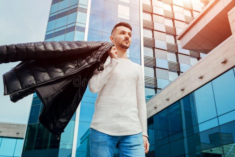 拿着他的外套和走在市中心的阿拉伯人 年轻人投掷在肩膀的外套 免版税库存照片