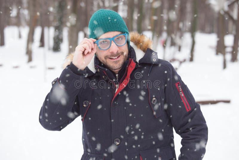 拿着他的太阳镜的一个年轻愉快的人的画象在雪天 库存照片