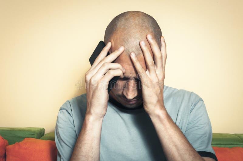 拿着他的头和手机用他的手的年轻秃头沮丧的人感觉挫败,因为他在他的上司以后失去了他的工作 免版税图库摄影