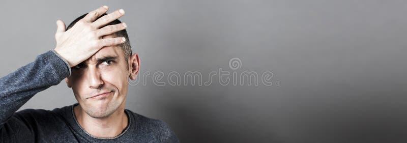 拿着他的头的迷茫的年轻人,有遗憾,灰色横幅 免版税库存图片