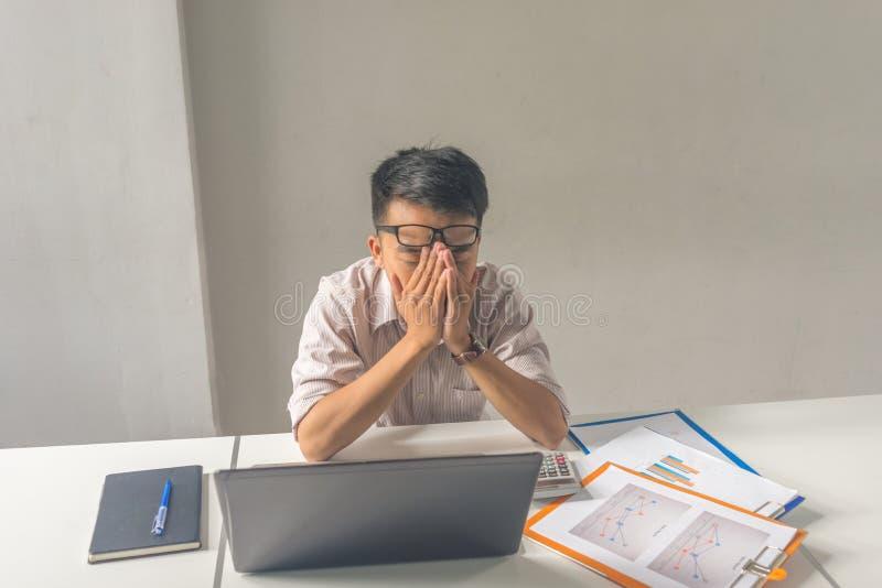 拿着他的头,对事务的忧虑的亚洲商人 免版税库存照片