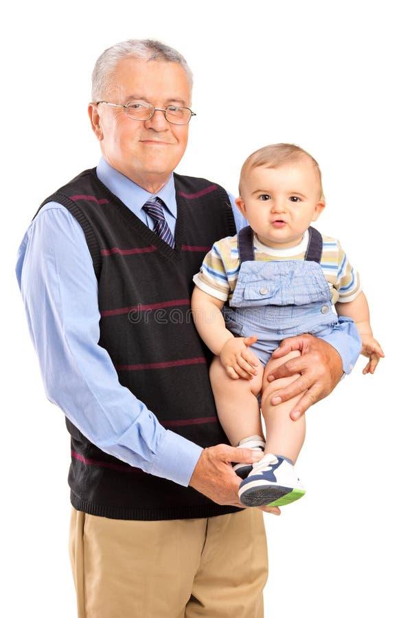 拿着他的孙子的祖父 库存图片