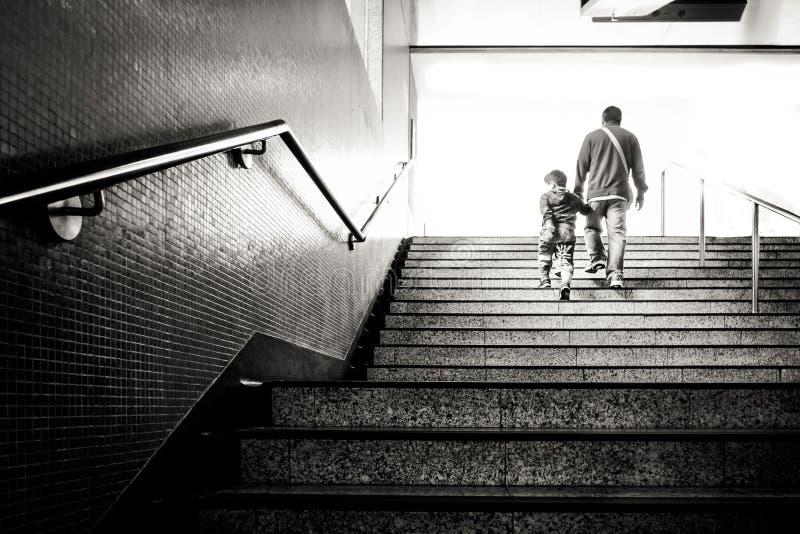 拿着他的孙的人走地铁车站楼梯 免版税库存照片