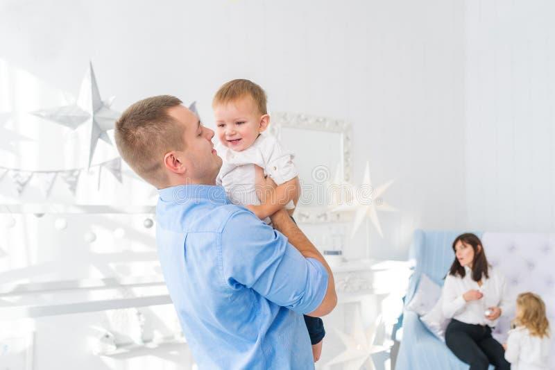拿着他的小儿子的年轻父亲 有小女儿的美丽的母亲是在背景 免版税库存照片