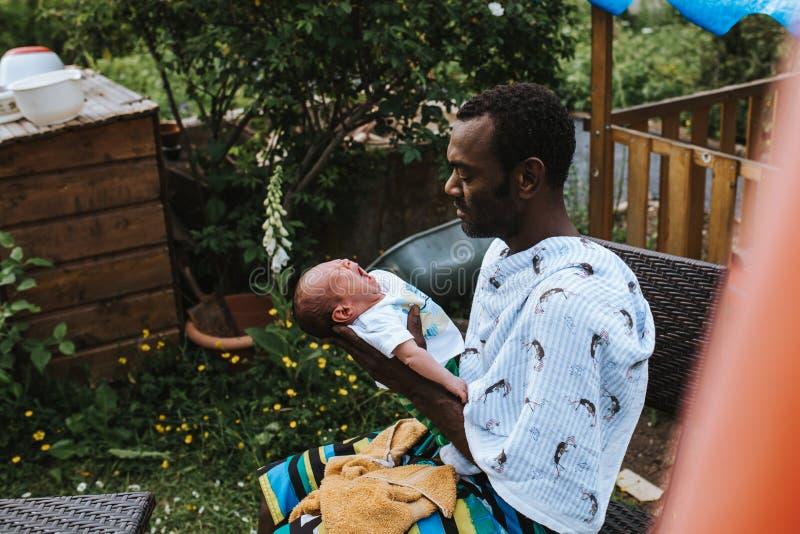 拿着他的混合的族种男婴的黑人父亲 免版税库存照片