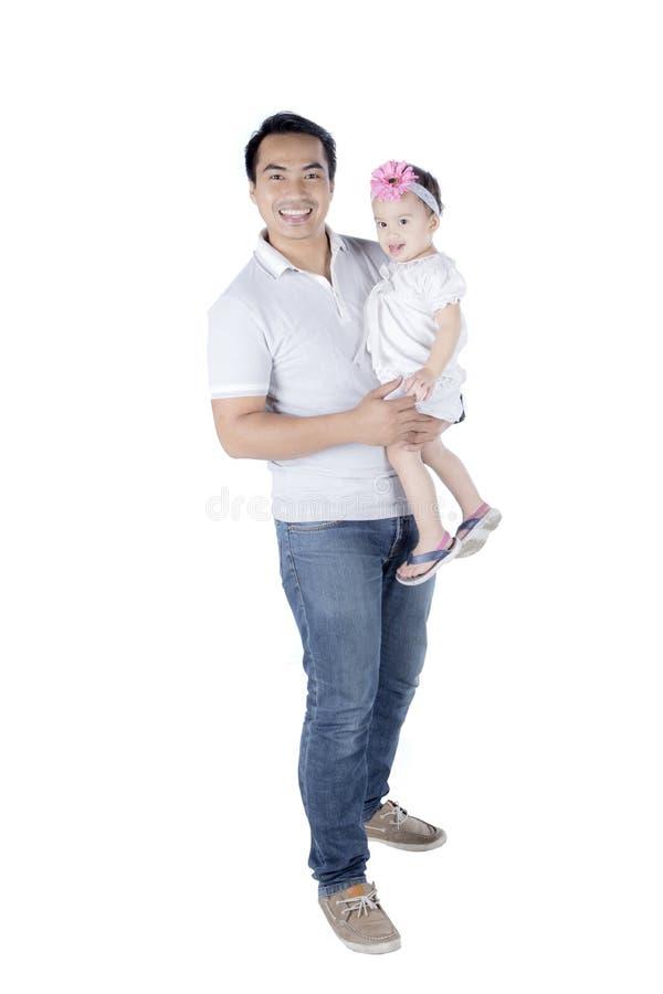 拿着他的演播室的年轻父亲女儿 免版税库存照片