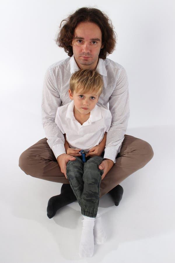 拿着他逗人喜爱的小男孩他的胳膊的和他的膝部的爸爸 库存图片