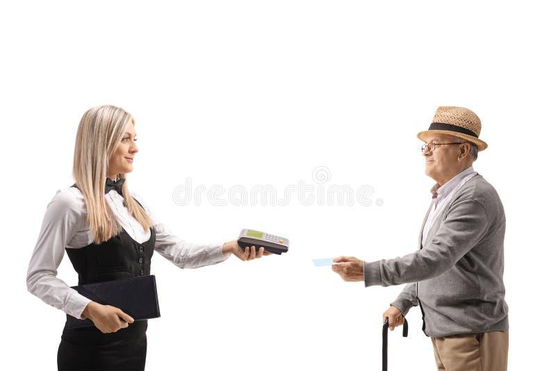 拿着付款终端和一份菜单与一个成熟人的女服务员 免版税图库摄影