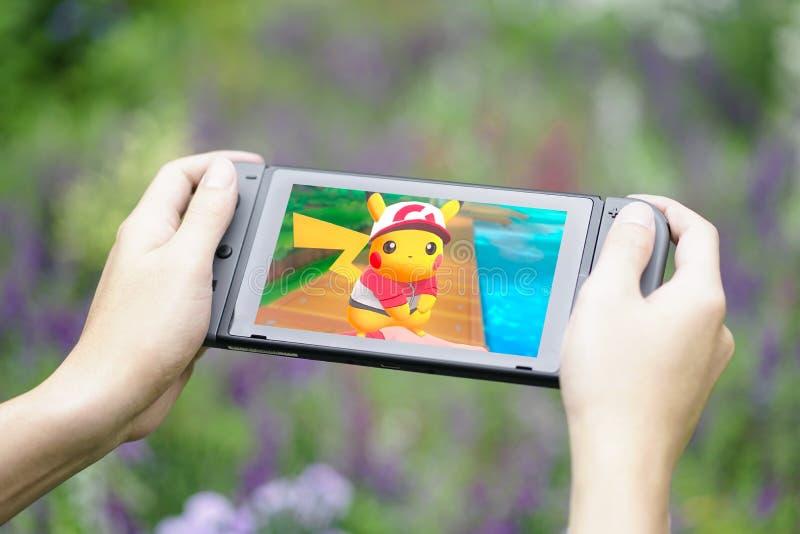 拿着任天堂开关的游戏玩家的手,当演奏Pokemon时在庭院里让我们走皮卡丘 免版税库存照片