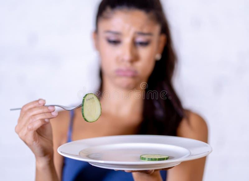 拿着伙计的沮丧的节食的妇女看在空的板材的小绿色菜 免版税图库摄影