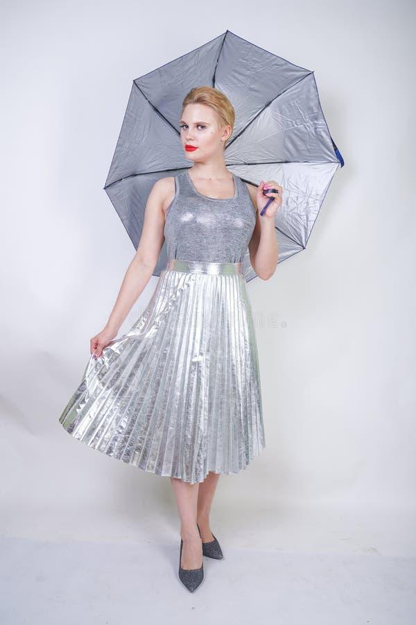 拿着伞和摆在在Stu的白色背景的一件现代城市金属银色礼服的逗人喜爱的胖的短发女孩 免版税库存图片