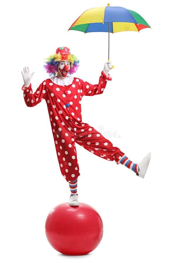 拿着伞和站立在一个巨型球的滑稽的小丑 图库摄影