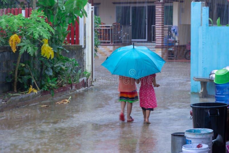 拿着伞和走沿街道的两个小女孩 库存图片