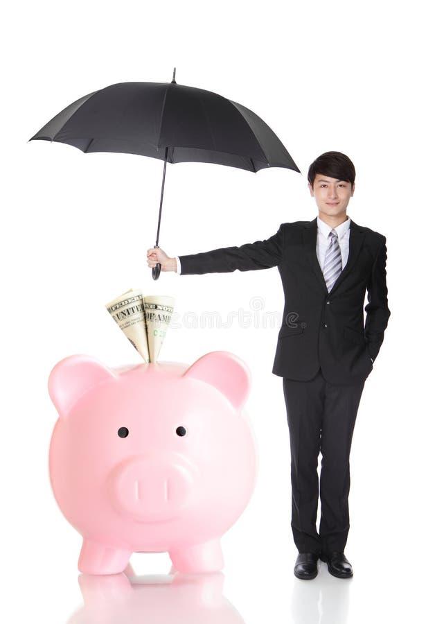 拿着伞的商人保护您的金钱 免版税库存照片