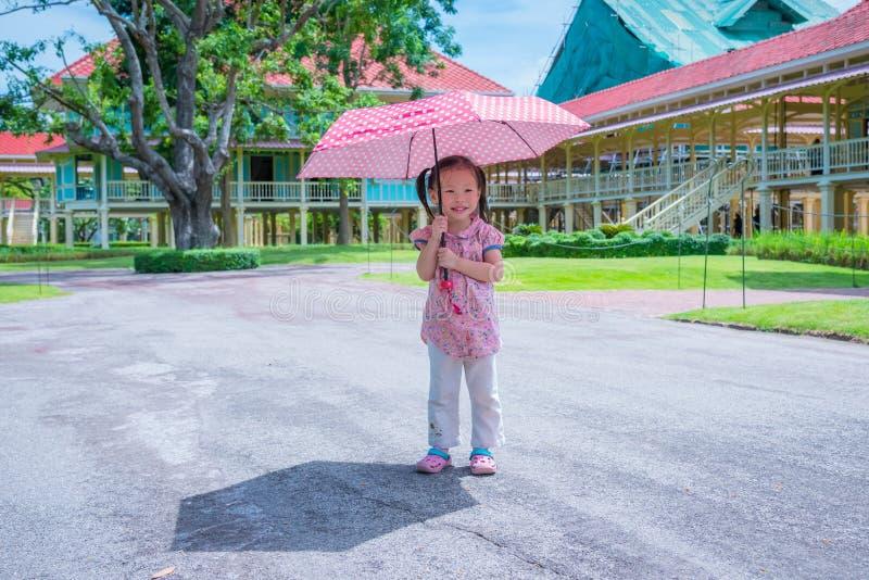 拿着伞的女孩在晴天 库存图片