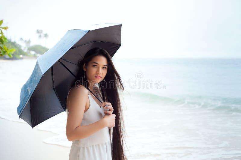 拿着伞的少妇在雨天在夏威夷海滩 免版税库存图片