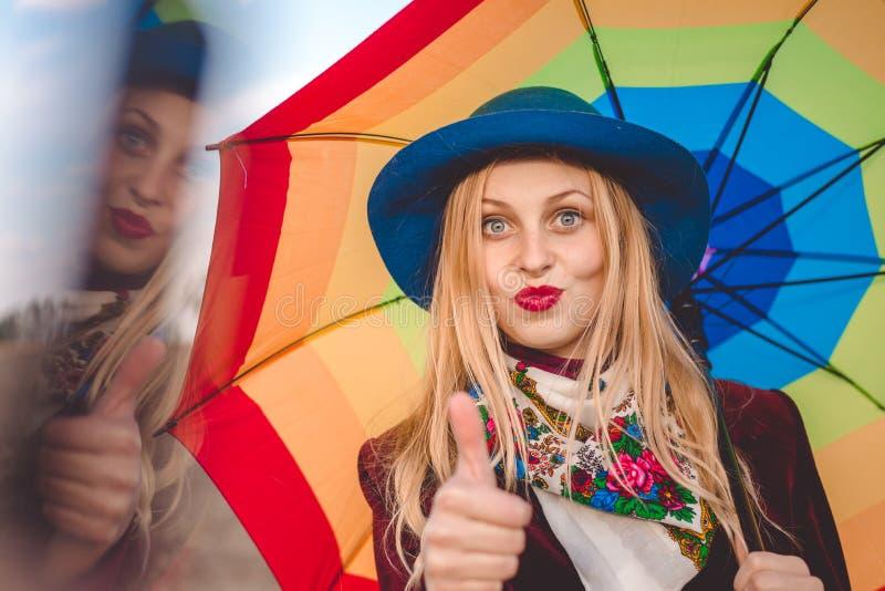 拿着伞的帽子的美丽的少妇和 免版税库存图片