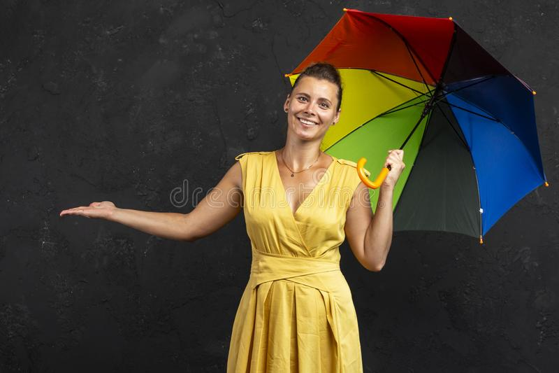 拿着伞的美丽的微笑的女孩 天气预报背景 相当有伞的愉快的女孩 免版税图库摄影