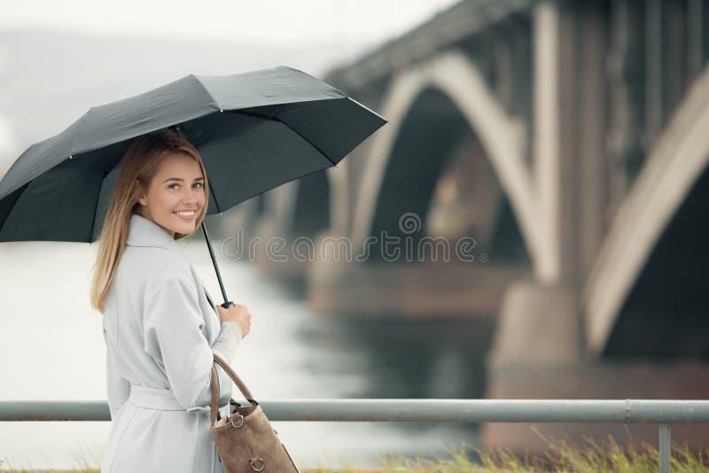拿着伞的蓝色外套的少妇 免版税库存图片