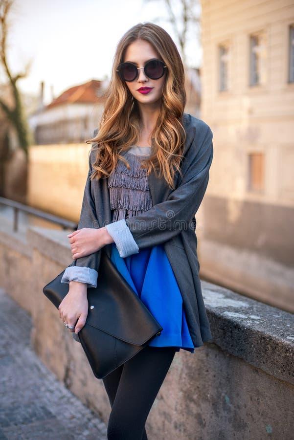 拿着传动器的美丽的时髦的女人在城市 免版税库存图片