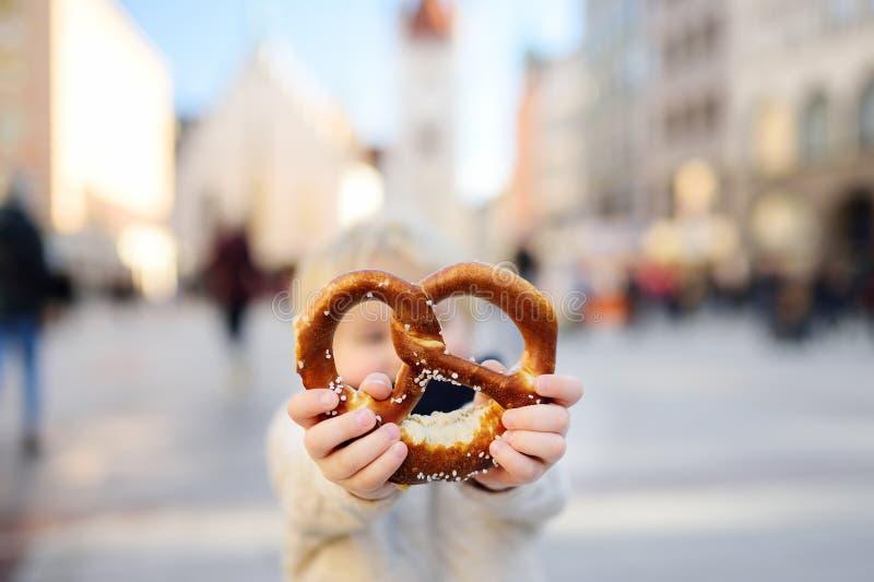 拿着传统巴法力亚椒盐脆饼的小游人在慕尼黑 免版税图库摄影