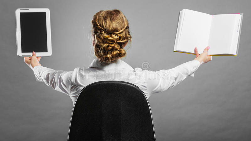 拿着传统书和e书读者的妇女 免版税库存图片