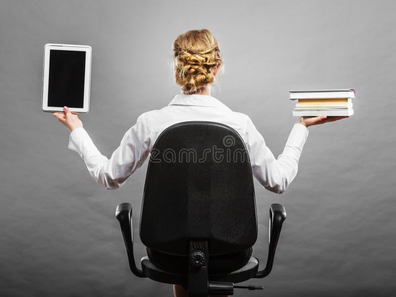 拿着传统书和e书读者的妇女 免版税库存照片