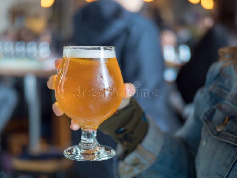 拿着低度黄啤酒一口威士忌酒IPA的妇女的近景 免版税库存照片
