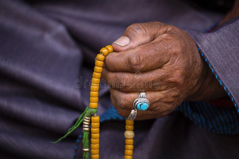 拿着佛教念珠的老西藏妇女在Hemis修道院,拉达克,印度里 手和念珠,关闭 库存照片