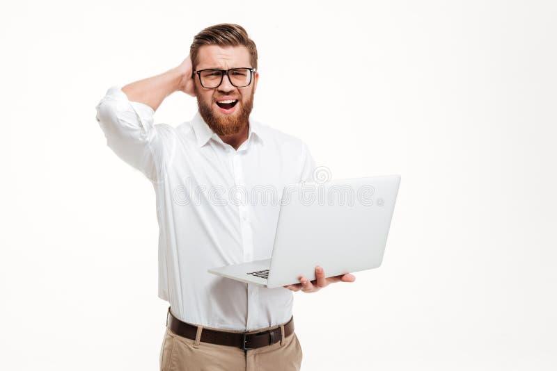 拿着便携式计算机和抓他的头的迷茫的有胡子的人 库存照片