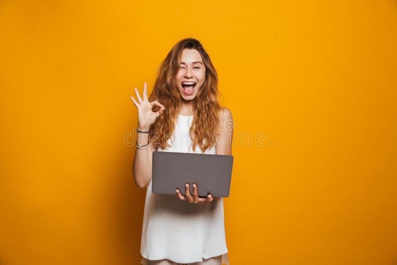 拿着便携式计算机的一个快乐的女孩的画象 免版税库存照片