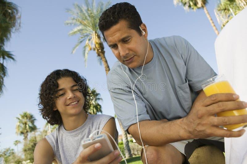 拿着便携式音乐播放父亲的男孩(13-15)听与耳机和拿着杯汁液。 库存照片