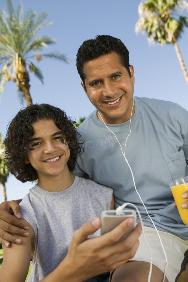 拿着便携式音乐播放父亲的男孩(13-15)听与耳机和拿着杯汁液正面图画象。 免版税库存图片
