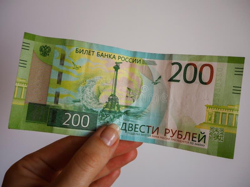 拿着俄罗斯的银行的一张新的二百卢布钞票妇女的手 库存照片