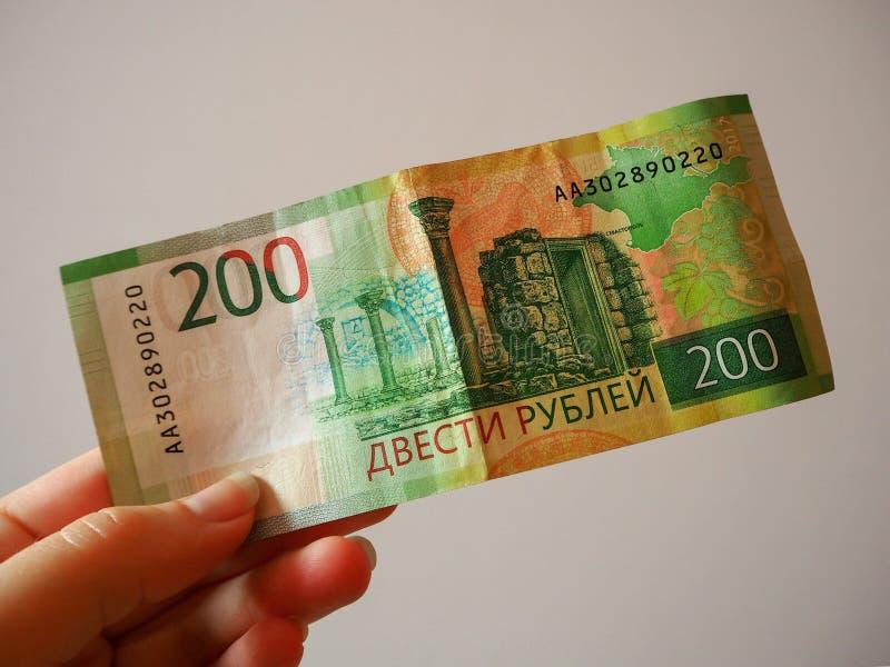 拿着俄罗斯的银行的一张新的二百卢布钞票妇女的手 钞票的反面 免版税库存图片