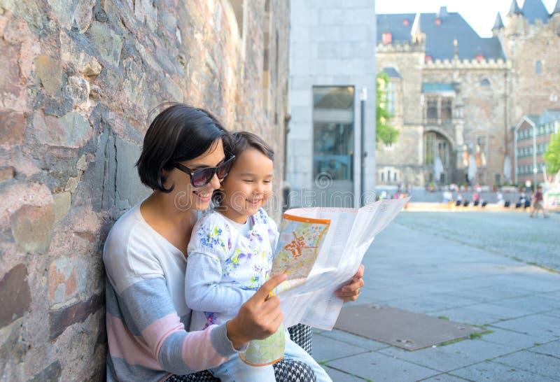拿着俏丽女儿的妇女和城市地图和微笑 库存图片