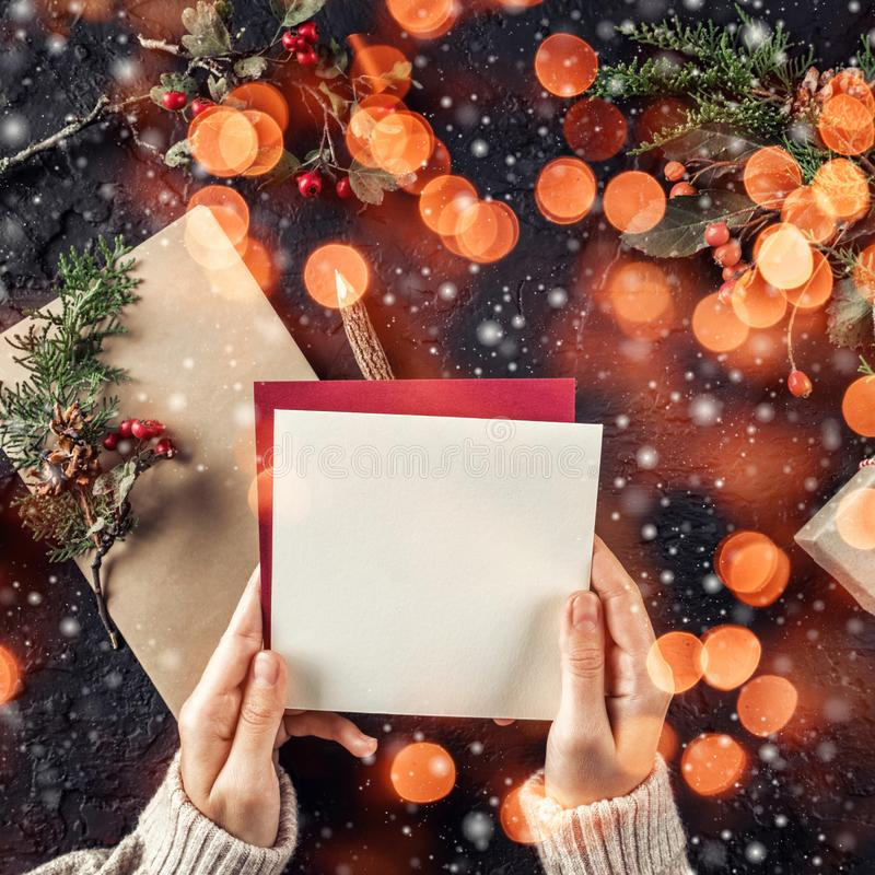 拿着信件的女性手对在吠声背景的圣诞老人与圣诞礼物,冷杉分支,杉木锥体 库存图片